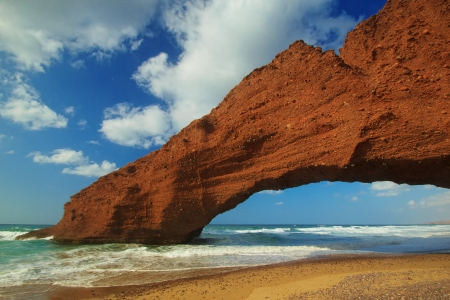 morocco: Amazing view of huge red cliffs with arch on the beach Legzira