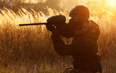 Paintball sport player in protective uniform and mask aiming gun before shooting at sunset