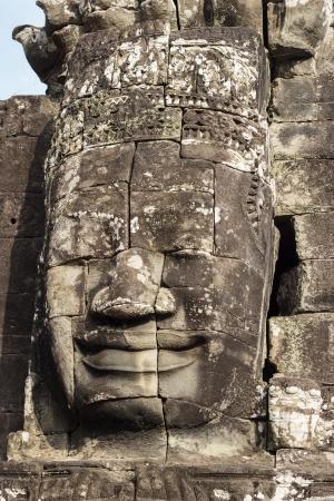 cabeza de buda: Cara de piedra de Buddha en las torres del templo de Bayon en Angkor Thom Foto de archivo