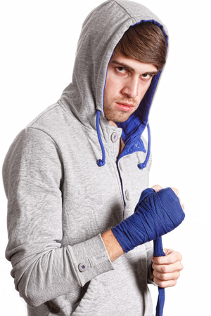 Boxer pulls the bandage isolated on white background photo
