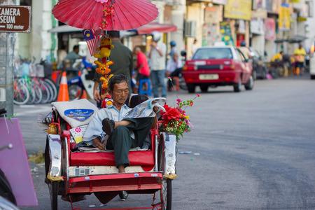 Georgetown, Maleisië - 19 januari Trishaw chauffeur te wachten op een klant op de straat op 19 januari 2014 in Georgetown, Maleisië De fietstaxi is een beroemde attractie voor toeristen naar de stad van Georgetown te zien Redactioneel