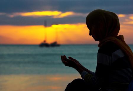 夕暮れ時に祈って若いイスラム教徒の女性