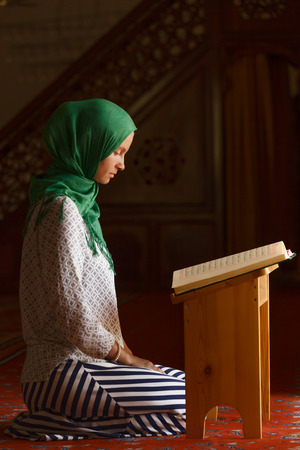 Young muslim woman reading Quran in turkish mosque photo