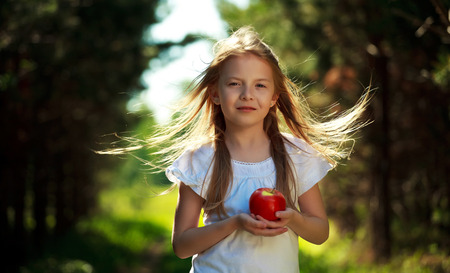blowing of the wind: Pretty little girl holding the apple and the hair is blowing in the wind Stock Photo
