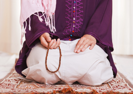 meditation pray religion: Young muslim girl with rosary praying on white background