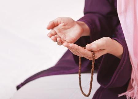 ロザリオを祈って白い背景の上の若いイスラム教徒の少女