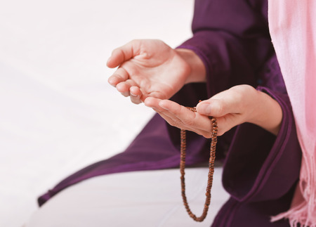 islamic pray: Young muslim girl with rosary praying on white background
