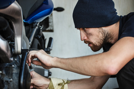 Serious young man repairing his motorcycle Stock Photo