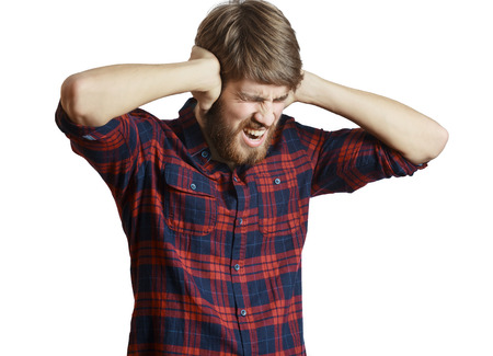 Screaming jonge man in het geruite overhemd sluit zijn oren, want te hard, geïsoleerd op een witte achtergrond