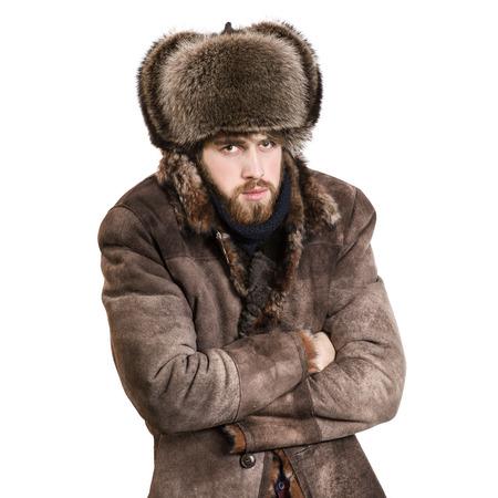 manteau de fourrure: Jeune homme barbu dans le manteau et chapeau oreillettes, sentir le froid, isolé sur un fond blanc