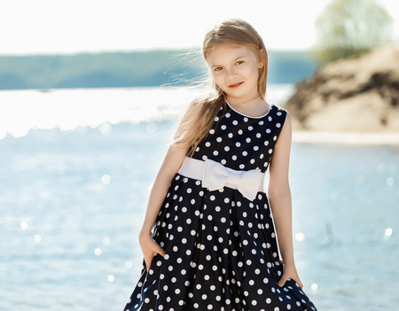 Cute little girl on the coast of the river