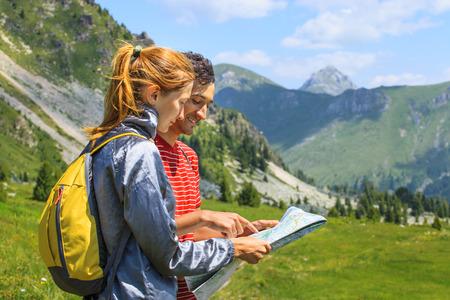 personas mirando: bella joven pareja planificar la ruta y mirando el mapa en las monta�as de Montenegro Foto de archivo