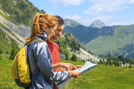 people: Young beautiful Couple planning the route and looking at the map in the mountains of Montenegro