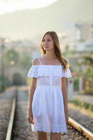 road shoulder: Serious young woman in white dress staying in the railway