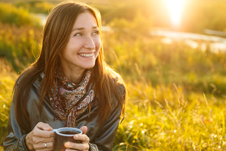 riendo: Joven y bella mujer con una taza de t� al aire libre Foto de archivo