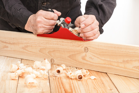 aged wood: Middle aged carpenter planing the surface of a plank of wood Stock Photo