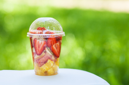 Sliced ??Fruits arranged in plastic cup