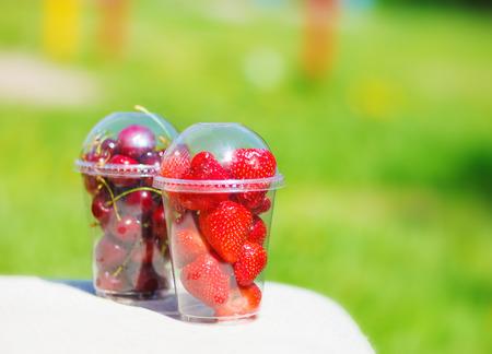ensalada de frutas: bayas de fresa y cereza en vaso de plástico en un parque de verano Foto de archivo