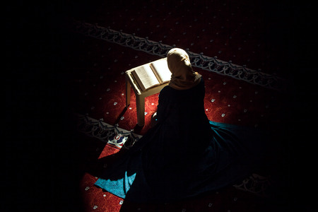 Young woman reading Quran in the mosque Stock Photo