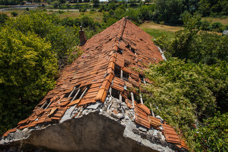 Old damaged roof of abandoned house Stock Photo
