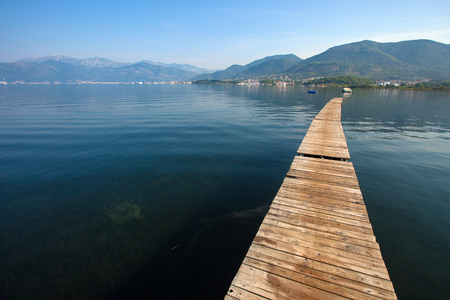 Serene wooden walkway in Boka Kotorska Bay, Tivat, Montenegro Stock Photo