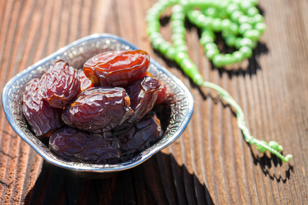 Beautiful bowl full of date fruits symbolizes Ramadan (Holy month of Muslims). On a wooden table