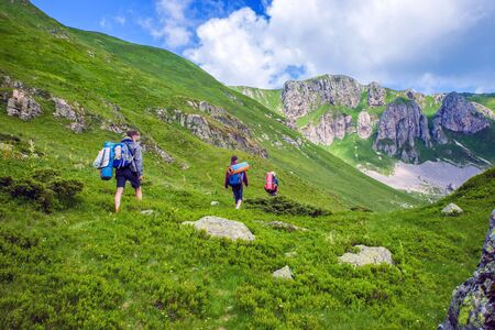 Group of hikers walking on a trail in a mountains Stock Photo