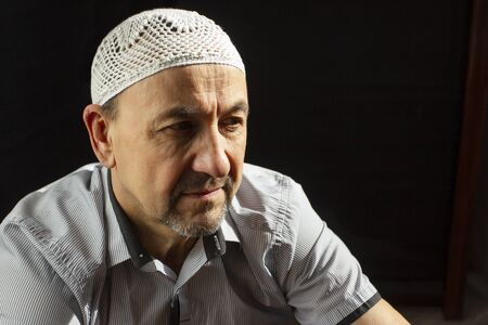 Portrait of Middle Aged muslim man in a mosque and sunlight falling from the window Stock Photo
