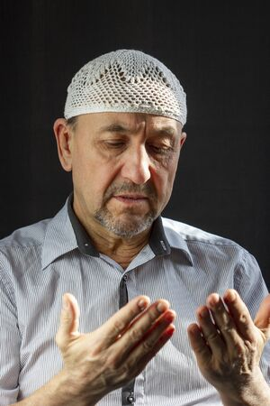 Middle Aged muslim man praying in the mosque and sunlight falling from the window Stock Photo