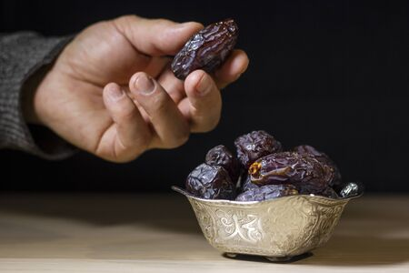 Man's Hand taking the date fruit from Beautiful bowl at iftar time, symbolizing Ramadan