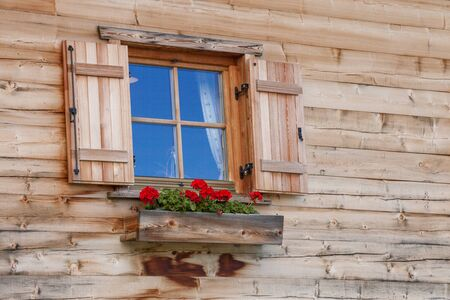 Cute window on a traditional wooden house in Alps with a flower pot