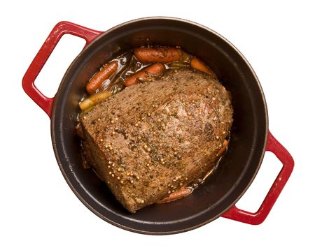 Beef roast with  carrots simmering in a red cast iron pot isolated on white