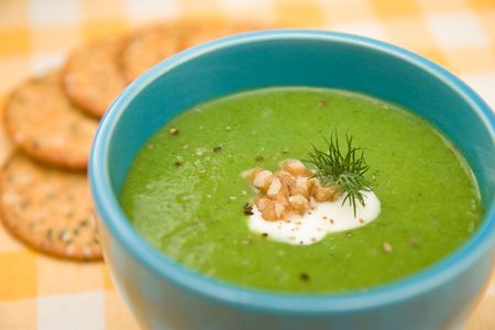 Fresh Cream of Broccoli soup garnished with walnuts & dill served with crackers photo