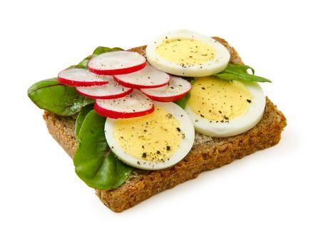 multi grain sandwich: Dark bread egg sandwich with lettuce & radishes on white background