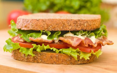 deli sandwich: BLT (Bacon, Lettuce, Tomato) sandwich with mayonnaise with fresh vegetables as background