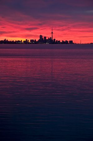 Toronto Skyline as seen from west, just before sunrise. The fiery red sky is reflecting in lake Ontario photo