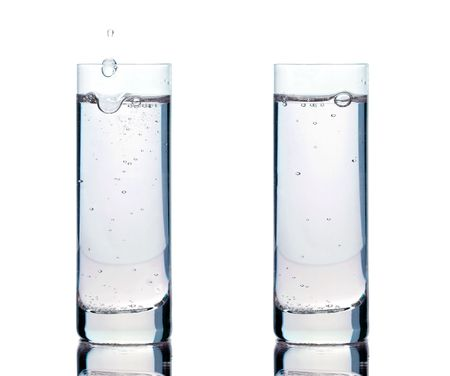 Two glasses of clean water with different bubble patterns. Drops of water falling into the left glass on white background photo