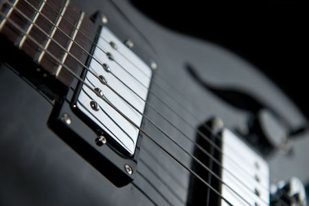 pickups: Detail of an electric guitar showing part of a fretboard and chrome pickups Stock Photo