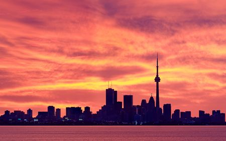 Torontos downtown core set against glowing orange sky moments before sunrise photo