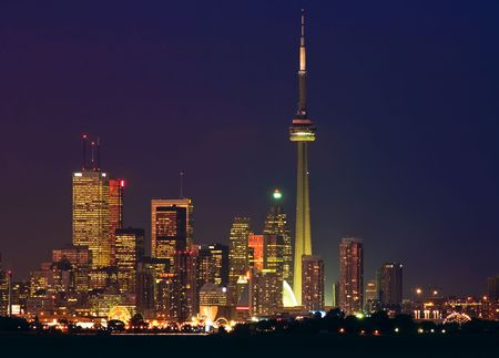 building cn tower: Brightly lit skyscrapers of Torontos financial district with the CN Tower and a silhouette of the waterfront Stock Photo