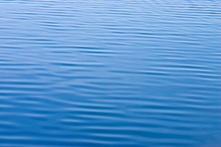 reflecting: Water surface with small waves reflecting clear blue sky