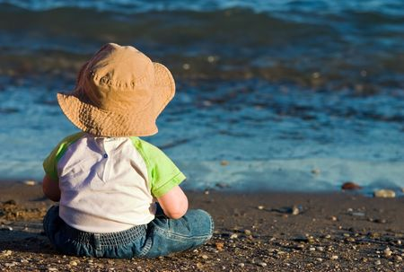 Toddler sitting on the beach looking at waves and dreaming about things to come