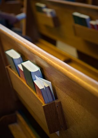 Church pews with focus on the prayer books