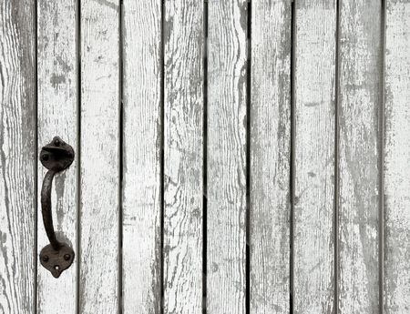 Detail of weathered wooden white gate with antique iron latch photo