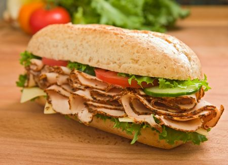 Delicious turkey breast  chicken breast submarine sandwich with lettuce, cheese, tomatoes and cucumbers photo