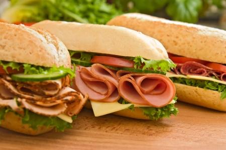 Drie verse sub sandwiches - turkey breast, ham & Zwitserse en salami op een snijplank. Focus op de ham sandwich