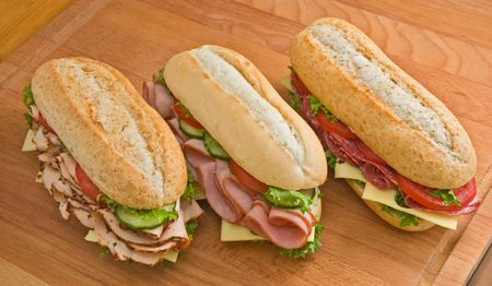 Three sandwiches - roasted turkey breast with cheese, cucumbers and tomatoes, ham and swiss cheese with tomatoes and salami, swiss cheese and tomatoes on a wooden board photo