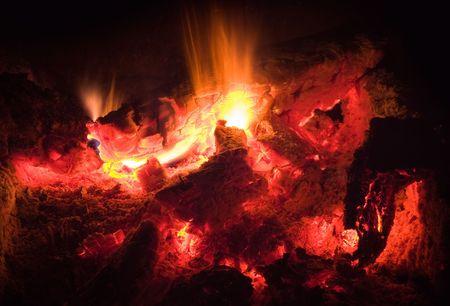 devour: Hot flames devour last pieces of wood in a campfire