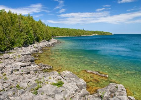 huron: Rocky coastline of Lake Huron with blue sky reflecting in the water Stock Photo