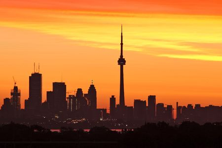 Torontos skyline lit by sun raising behind the buildings photo
